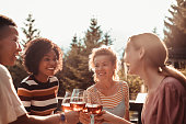 Close up of a group of friends enjoying wine after a dinner on the patio in the woods