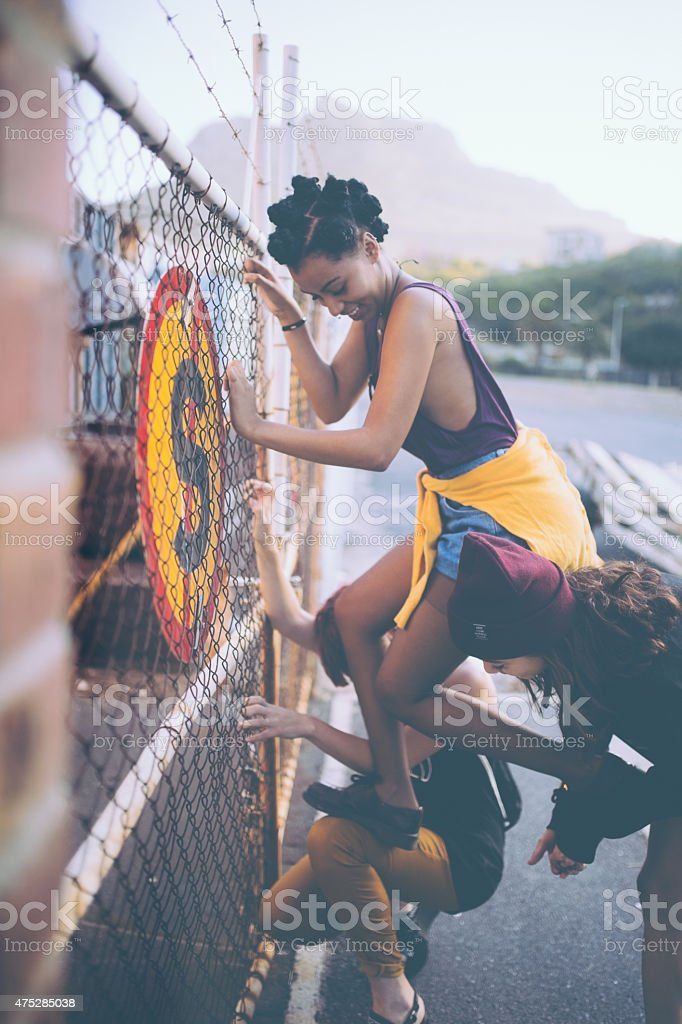 Friends helping Afro grunge girl climb urban fence stock photo