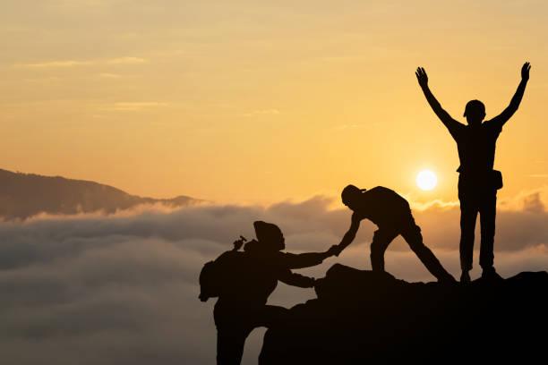 친구는 서로 팀워크, 멋진 여름 석양 동안 산의 상단에 도달 하려고 돕는. - 등정 뉴스 사진 이미지