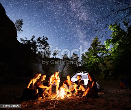678554980 istock photo Friends hikers resting beside camp, campfire, tent at night 1128638652