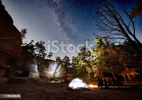 678554980 istock photo Friends hikers resting beside camp, campfire, tent at night 1128638656