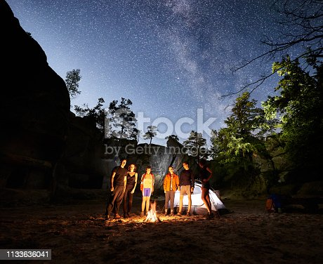 678554980 istock photo Friends hikers resting beside camp, campfire, tent at night 1133636041