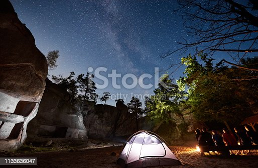 678554980 istock photo Friends hikers resting beside camp, campfire, tent at night 1133636047
