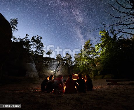 678554980 istock photo Friends hikers resting beside camp, campfire, tent at night 1133636068
