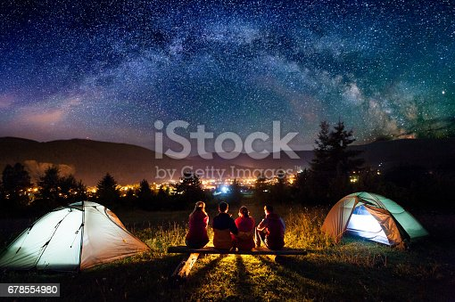 678554980istockphoto Friends hikers sitting beside camp and tents in the night 678554980