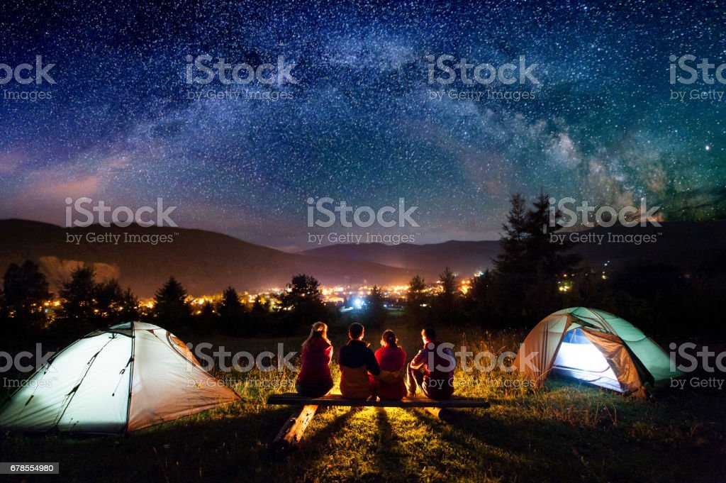 Friends hikers sitting beside camp and tents in the night stock photo