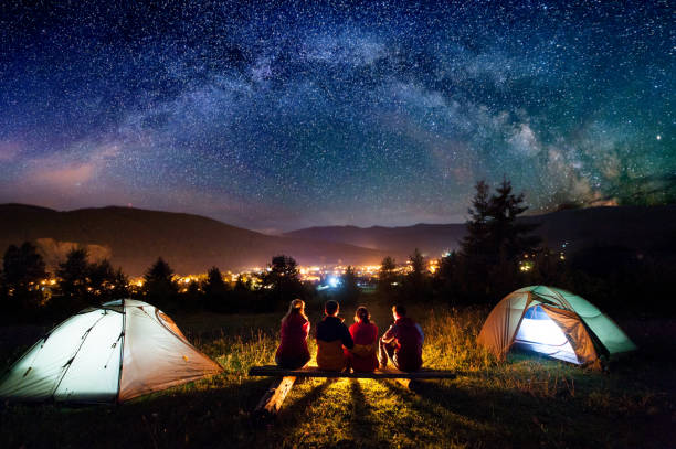 friends hikers sitting beside camp and tents in the night - camping stock photos and pictures