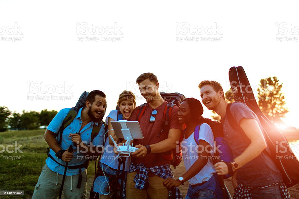 Friends Hiking And Piloting Multicopter Outdoors. stock photo