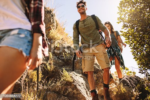 Young man with two women friends walking through rocky trail. Friends hiking on rocky mountain trail.
