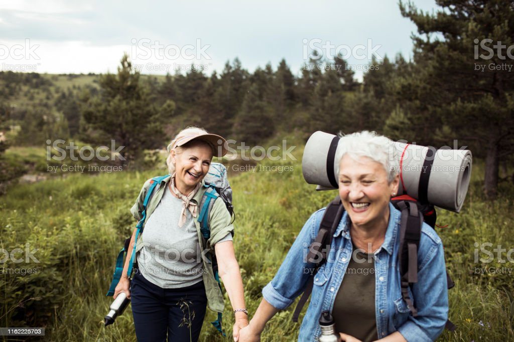 Friends Hiking Close up of two senior female friends hiking together 60-69 Years Stock Photo
