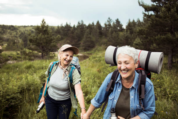 Friends Hiking Close up of two senior female friends hiking together lgbtqi people stock pictures, royalty-free photos & images