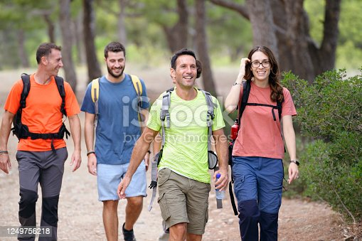 Close-up of approaching middle-aged Spanish friends backpacking through tree area on Mediterranean coastal trail.