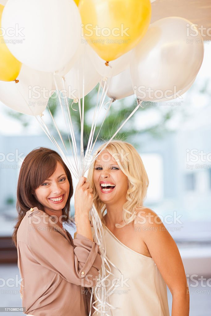 Friends holding balloons stock photo