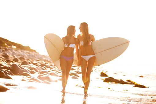 Friends holding hands as they return from a surf