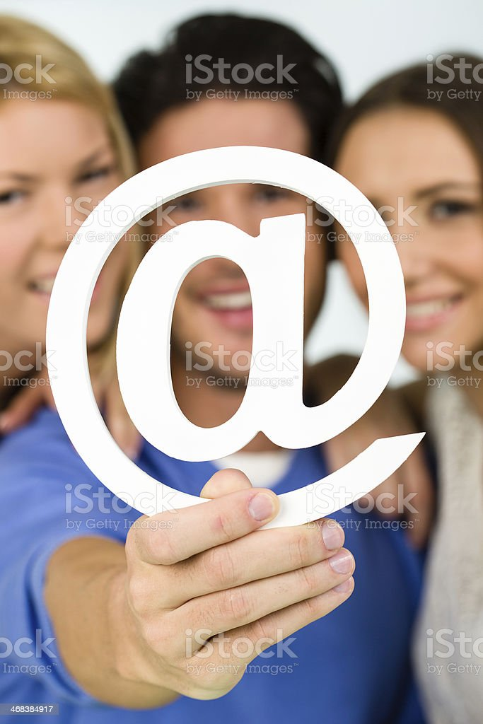 """Friends holding """"at"""" symbol royalty-free stock photo"""