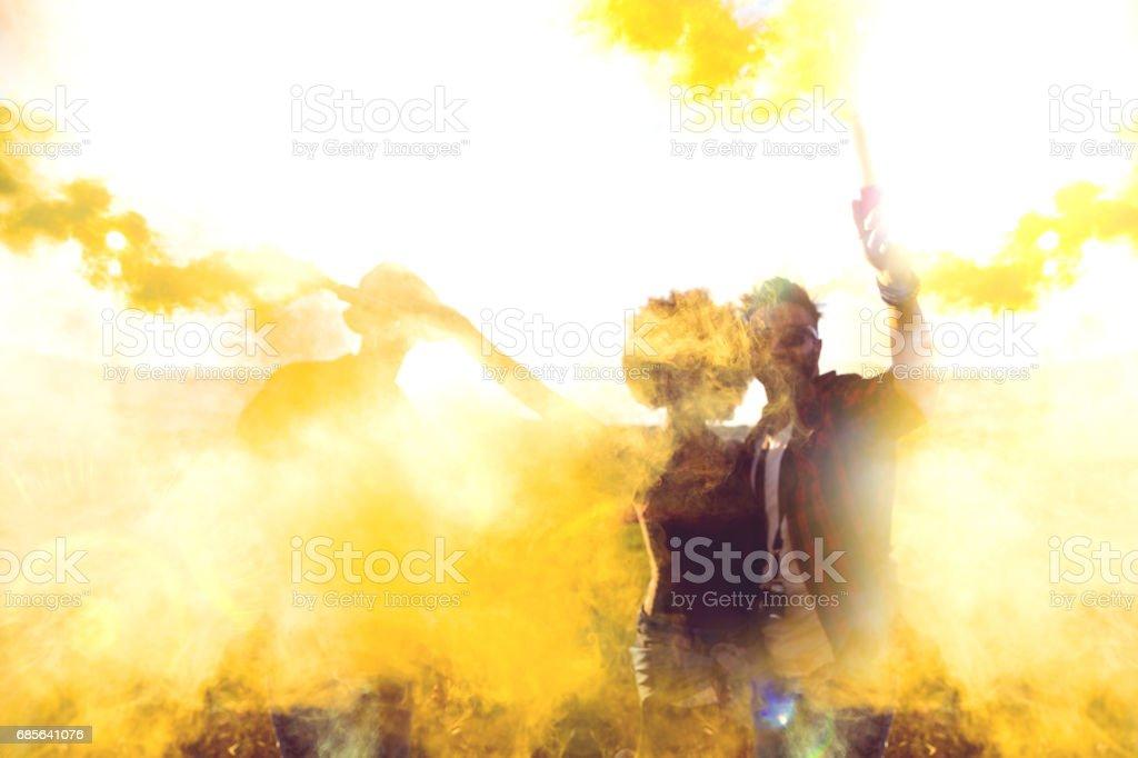 Friends holding smoke bombs having fun in a field foto de stock royalty-free