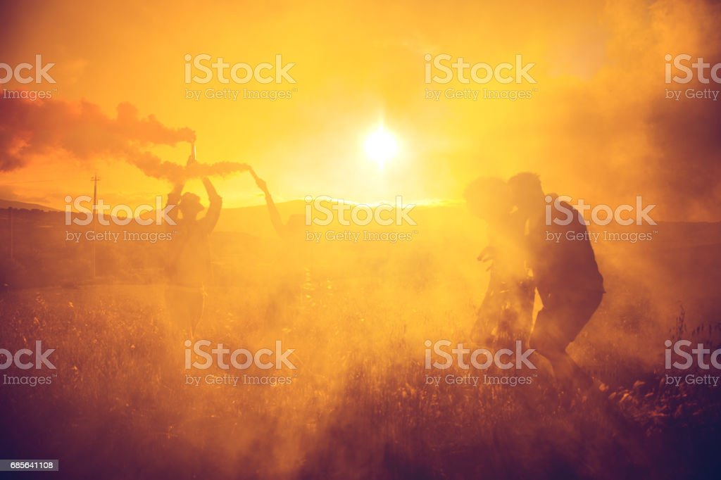 Friends holding smoke bombs having fun in a field royalty-free stock photo