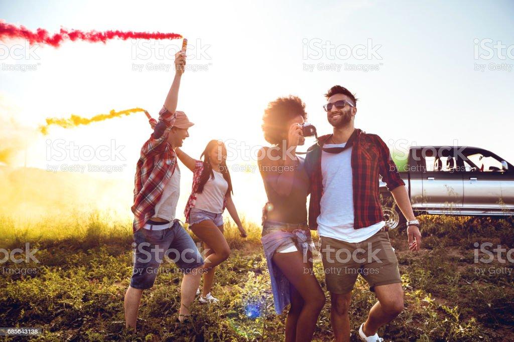 朋友們捧煙霧彈欄位中獲得樂趣 免版稅 stock photo