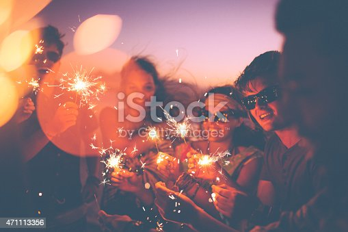 Group of friends having a beachparty together and celebrating with sparklers in the  twilight