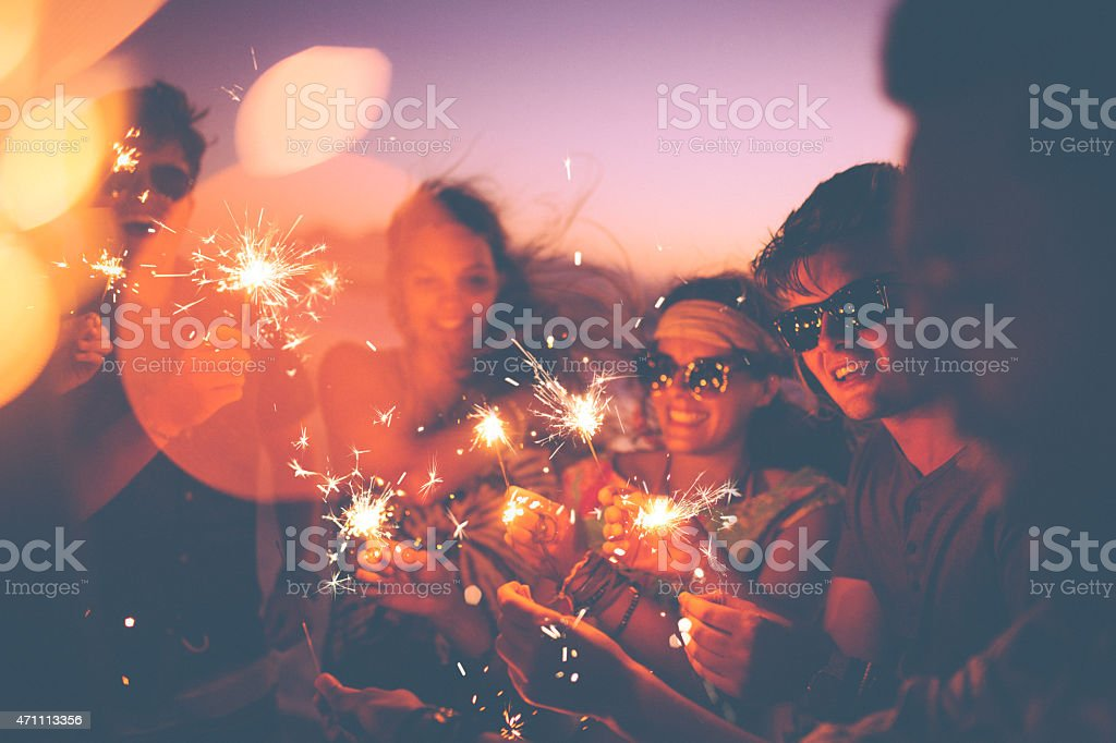 Friends holding sparklers at a beachparty at twilight stock photo