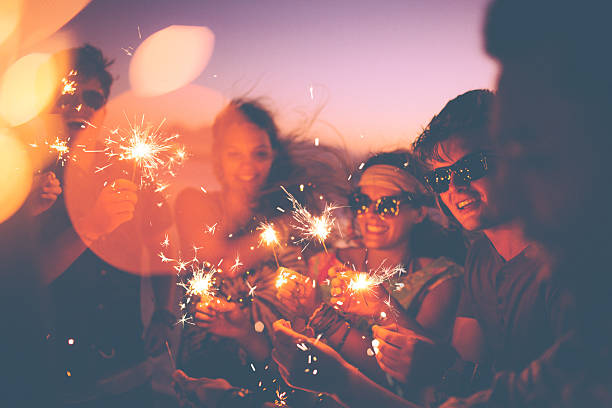 Friends holding sparklers at a beachparty at twilight Group of friends having a beachparty together and celebrating with sparklers in the  twilight independence day holiday stock pictures, royalty-free photos & images