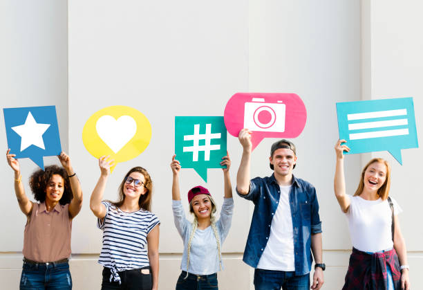 Friends holding up thought bubbles with social media concept icons stock photo