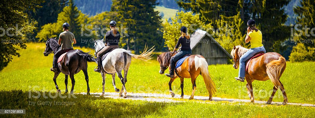 Friends Horseback Riding in the Countryside stock photo