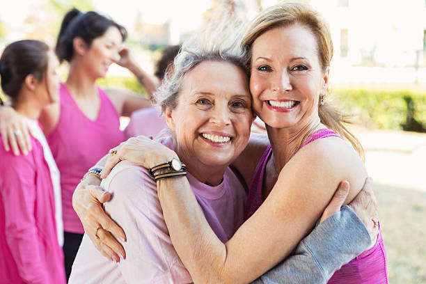 Friends hug at charity event stock photo