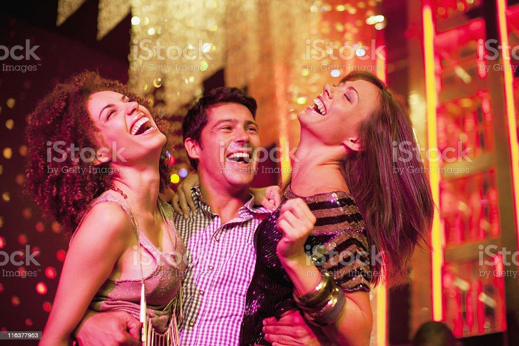 Friends hugging in nightclub stock photo
