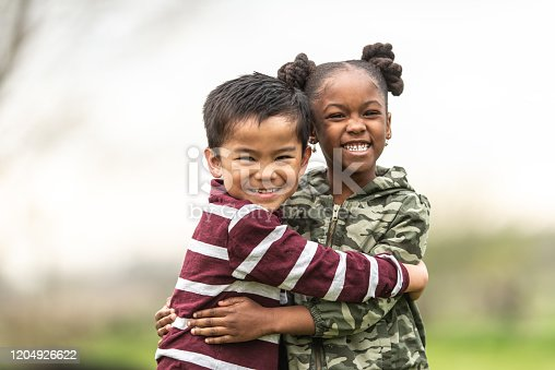A young Asian boy and a sweet African girl warmly hug each other while outside on a cool fall day.  They are each dressed casually in autumn clothing and smiling as they enjoy their time together and the fresh air.
