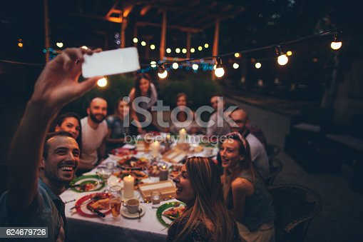 Photo of a cheerful friends having gathering in a local bistro, taking photos with a mobile phone