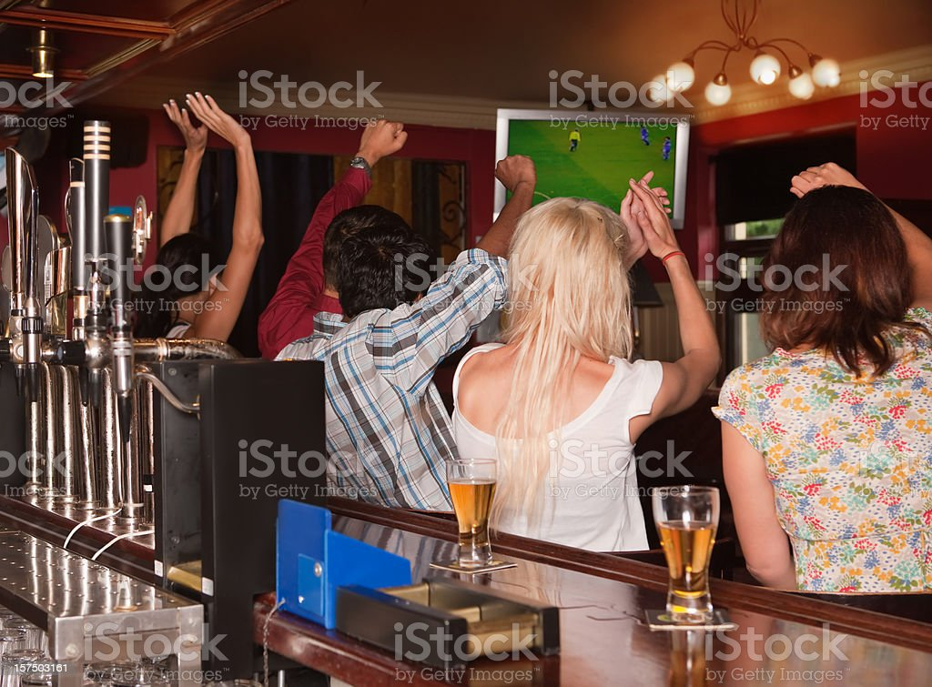 Friends in a pub watching football stock photo