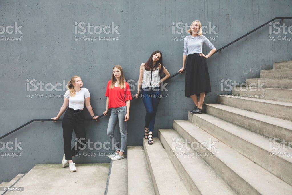 Friends in a row against against wall stock photo