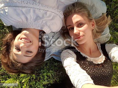 Selfie portrait of two young Caucasian girl friends lying on a grass on a sunny summer day.