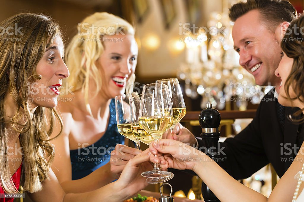 Friends in a very good restaurant clink glasses royalty-free stock photo