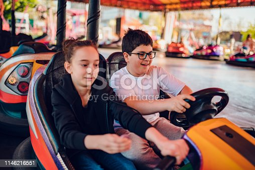 915609494istockphoto Friends in amusement park driving bumper car 1146216551