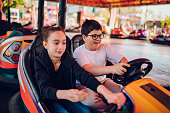 Boy wearing eyeglasses driving bumper car with her girlfriend in amusement park and having fun
