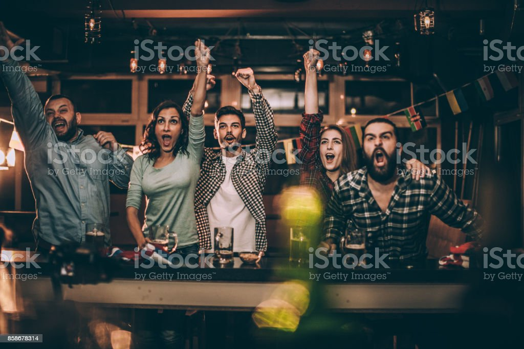 Friends in bar watching game stock photo