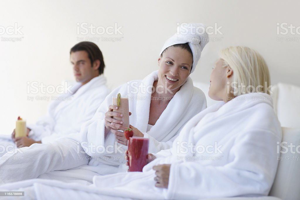 Friends in bathrobes drinking smoothies at spa royalty-free stock photo