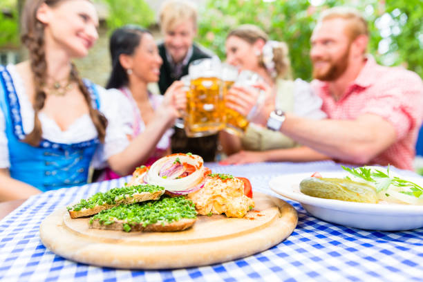 Friends in beer garden with drink and Bavarian appetizers stock photo