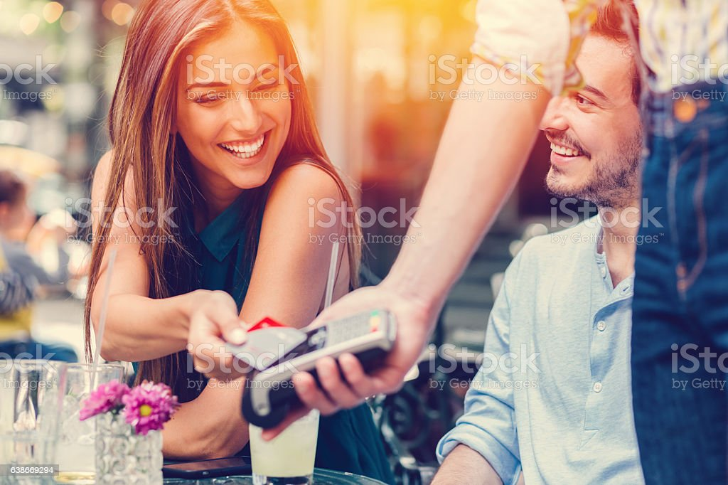 Friends in cafe paying contactless stock photo