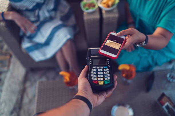 Friends in cafe paying contactless with smartphone stock photo