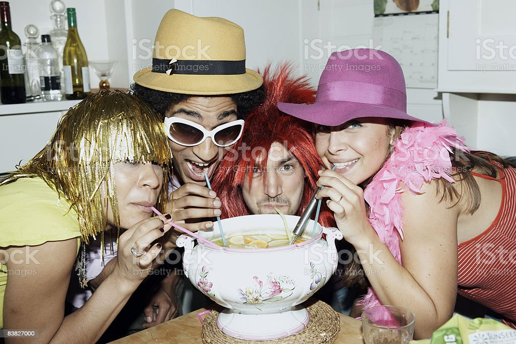 Friends in costume drinking punch through straws royalty-free stock photo