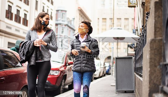 Two diverse young female friends smiling under face masks while walking together with takeaway coffees along a city sidewalk