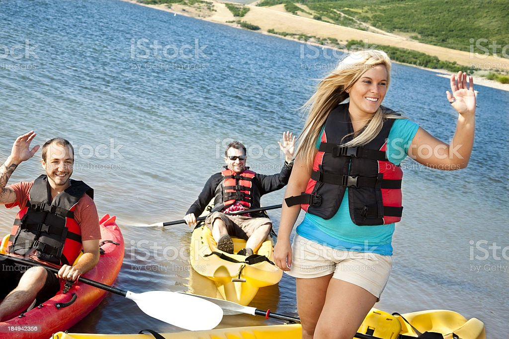 Friends in Kayaks waving toward the lake, river banks. royalty-free stock photo