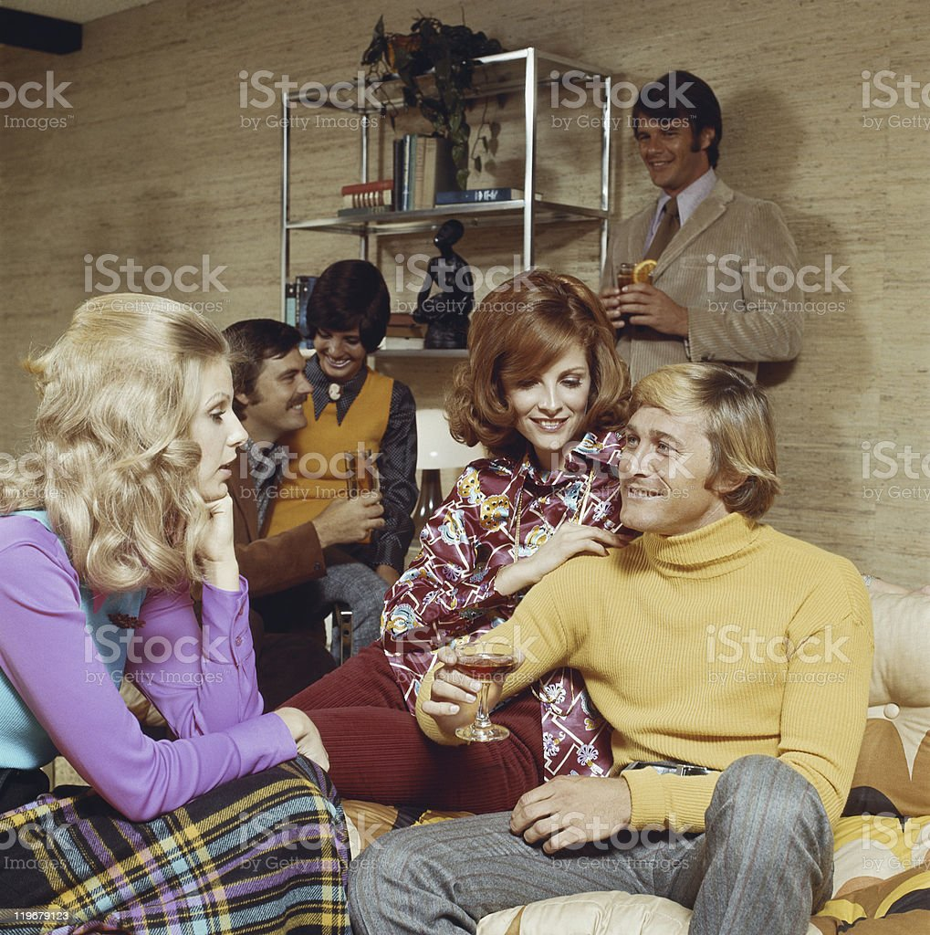 Friends in living room talking and enjoying drinks stock photo