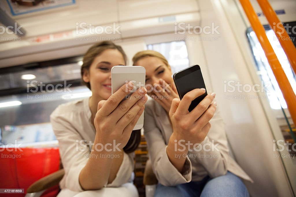 Friends in London Overground Two smiling young women sitting in a London overground train and using their smart phones. Close up on human hands. 20-24 Years Stock Photo