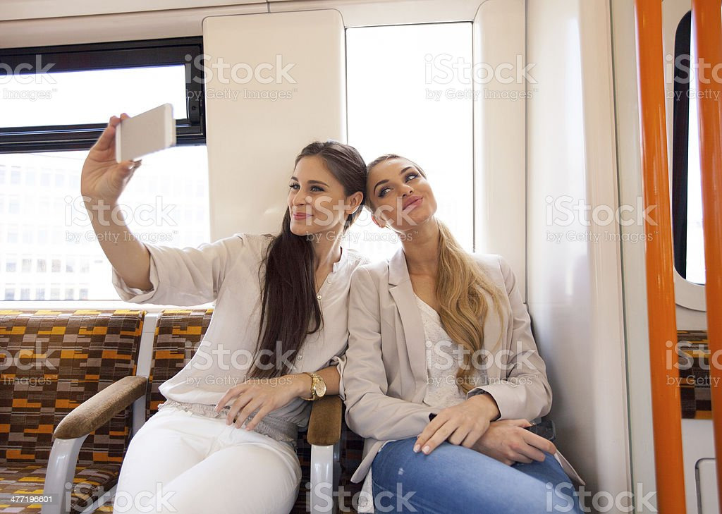 Friends in London Overground Two smiling young women sitting in a London overground train and taking a self picture using a smart phone. 20-24 Years Stock Photo