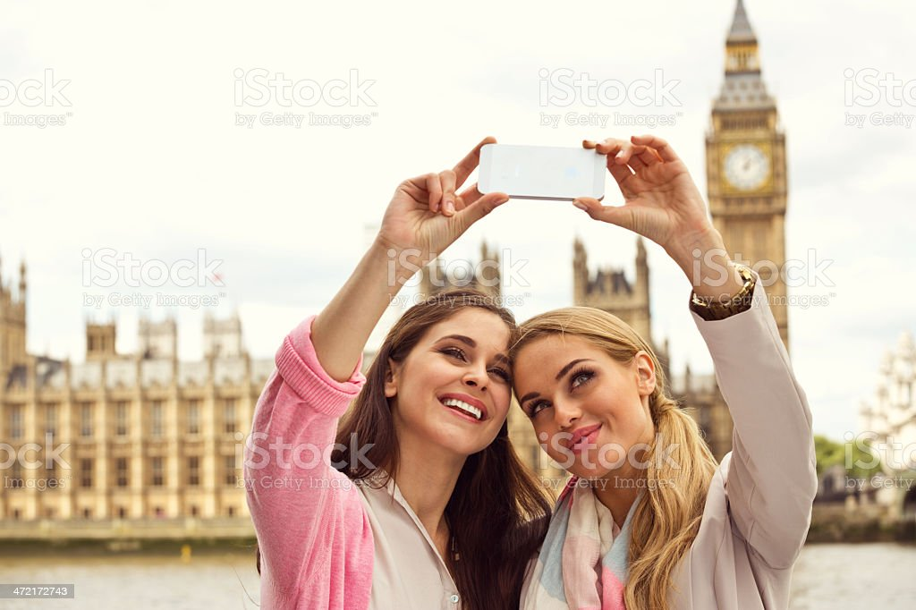 Friends in London Outdoor portrait of two happy women taking a self picture using a smart phone with Houses of Parliament and Big Ben in the background. 20-24 Years Stock Photo