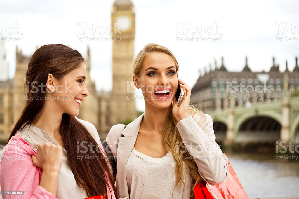 Friends in London Outdoor portrait of two happy London tourists, the blonde talking on phone. House of Parliament and Big Ben in the background. 20-24 Years Stock Photo